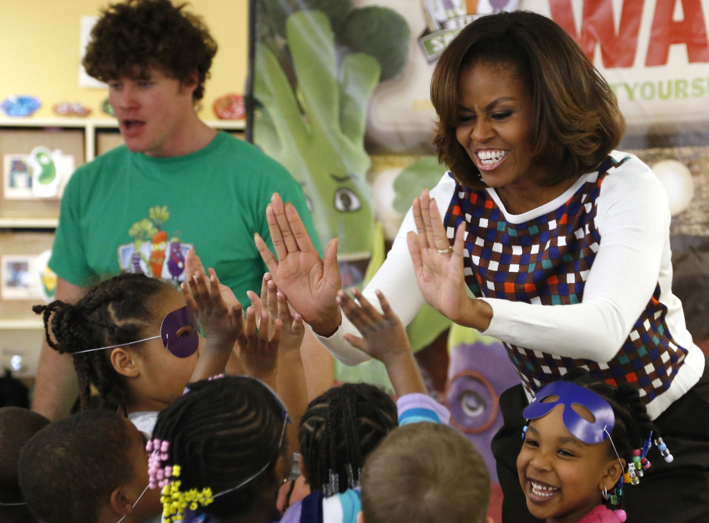 U.S. first lady Michelle Obama gives out high fives after learning a dance and exercise with children at a La Petite Academy chid care center in Bowie, Maryland, February 27, 2014. Obama made the visit to highlight the commitment that the parent company, Learning Care Group, has made to the child care best practices in her Let's Move! Initiative for children's health. REUTERS/Jonathan Ernst (UNITED STATES - Tags: POLITICS HEALTH EDUCATION) - RTR3FSR1